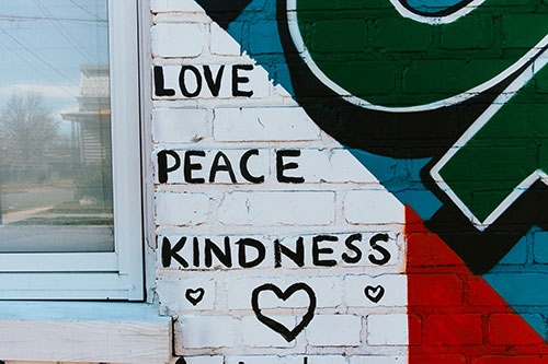 Part of a Giving Wall mural showing the words Love, Peace, and Kindness