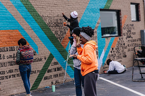 A few folks laughing while painting the Giving Wall mural at Perch