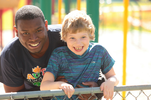 A man and boy smiling in a park