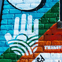 The Giving Wall logo painted on a mural